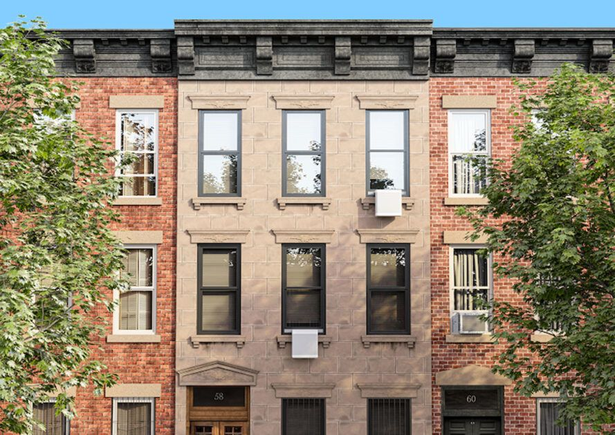 A brownstone building with a white AC window box hanging down from a window.