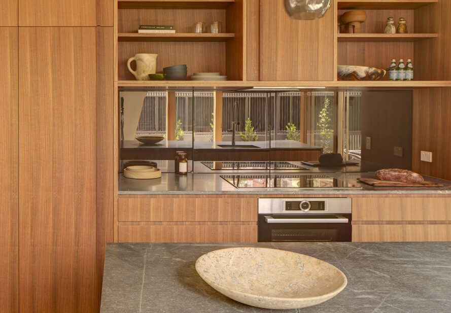 A kitchen with wood cabinets and slate countertops.