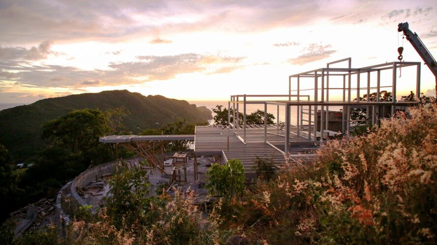 steel house frame on an island at sunset