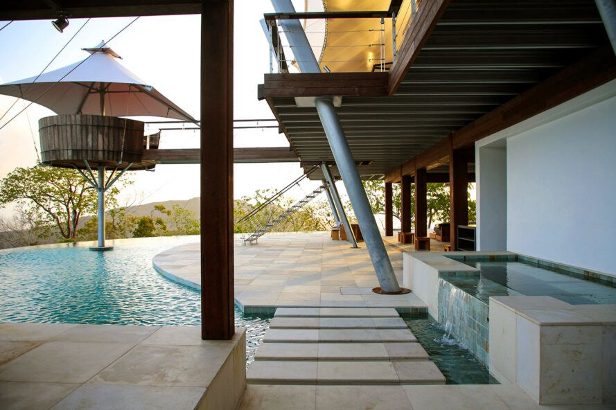 concrete path to patio surrounded by a pool