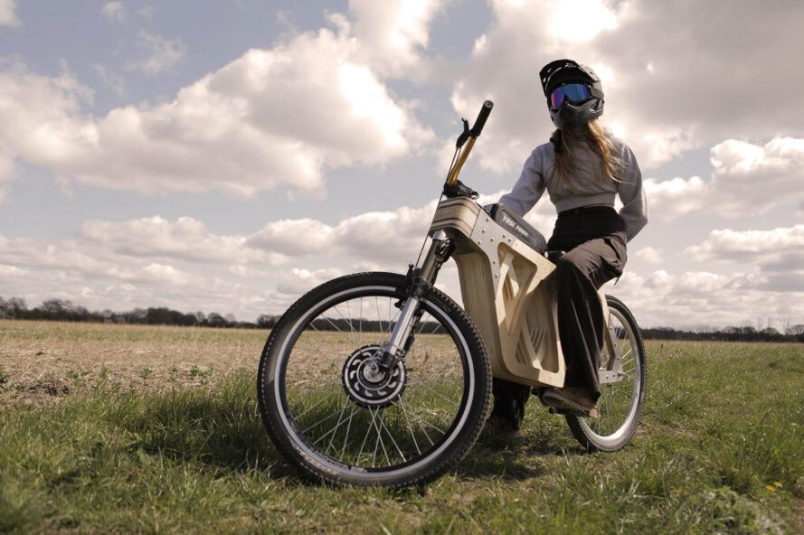 A person in a bike helmet posed on a wooden e-bike.