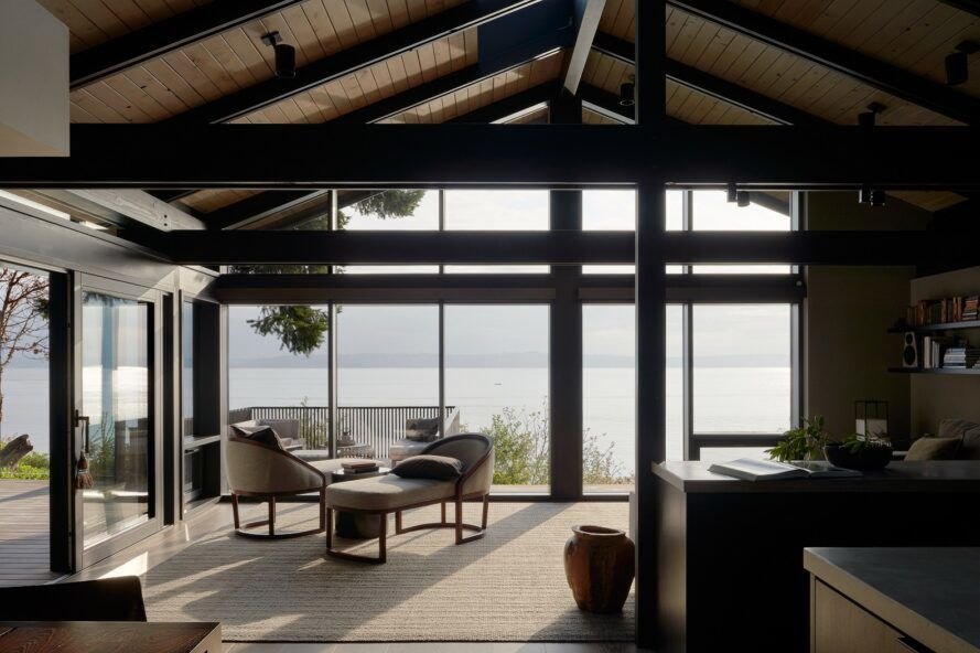 A sitting room with two off-white chairs and a matching coffee table. Floor-to-ceiling windows look out onto the Puget Sound.