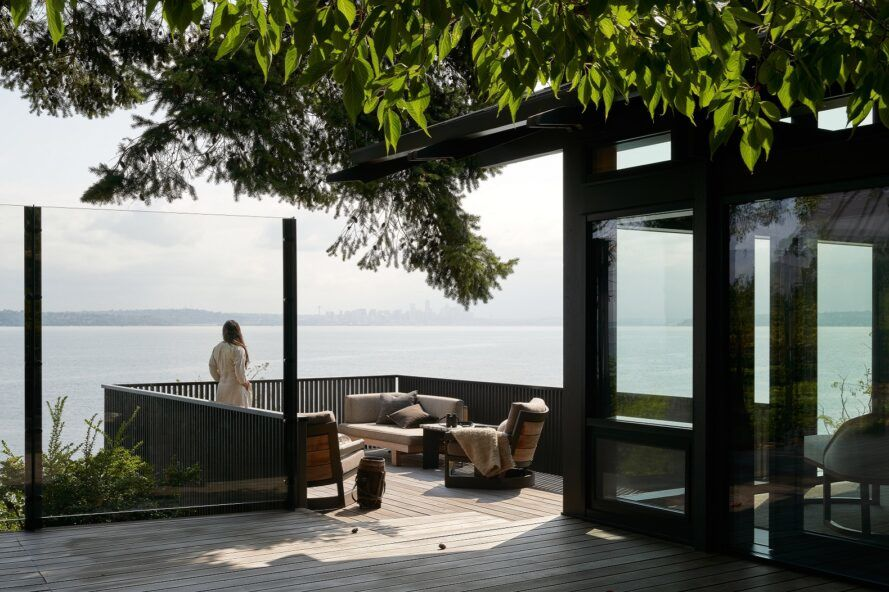 A wood deck with a person standing and looking out on the Puget Sound.