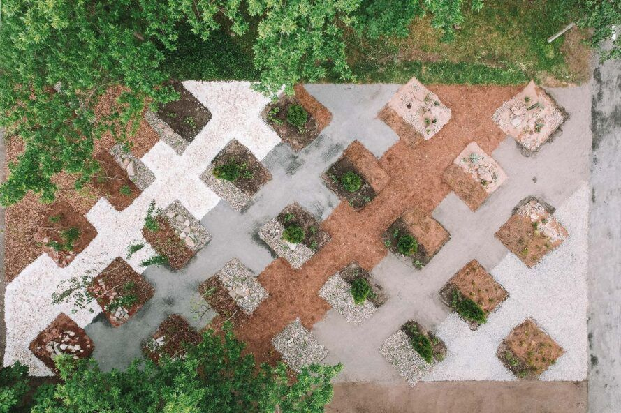 An overhead view of a garden with hard tile surrounding small square plots of land where trees and shrubs are planted.