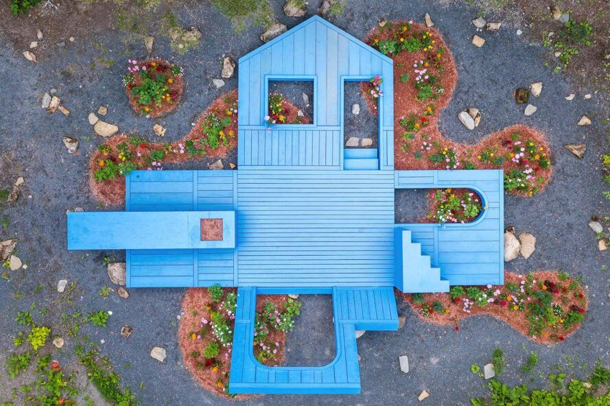 An overhead view of a blue house opened up to look like an exploded diagram of a house.