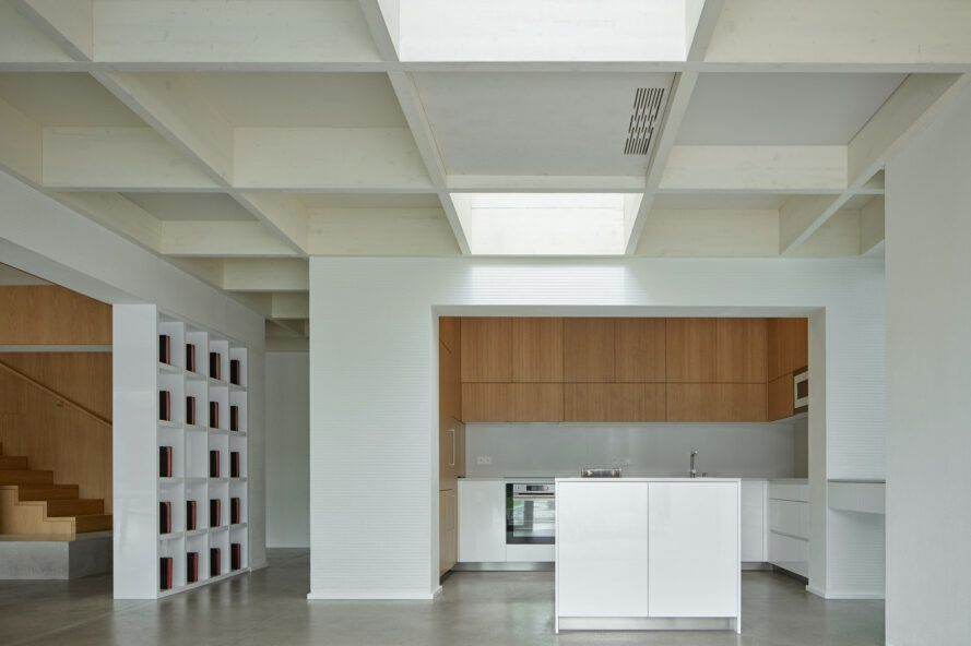 A kitchen with white walls, ceilings, floors and counters. The cabinets are a light-toned wood.