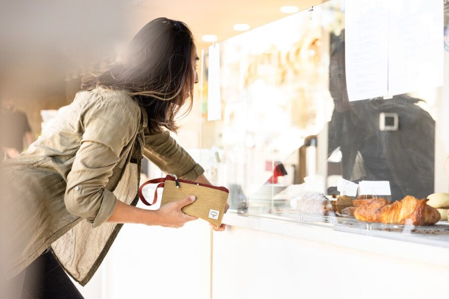 A person holding a tan zip bag and looking in a window.