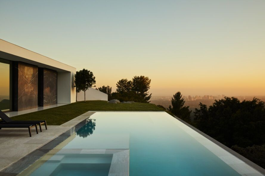 House at sunset with an infinity pool overlooking a city.