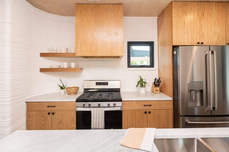 A kitchen with wood cabinets, a stove and steel fridge.