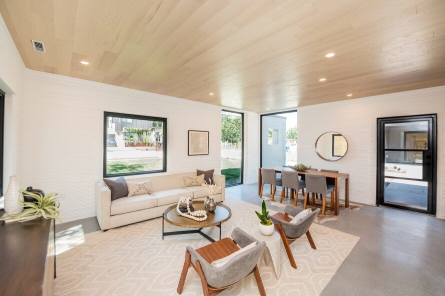 A neutral living room with white walls, a white carpet, wooden ceilings, a white sofa and gray chairs.