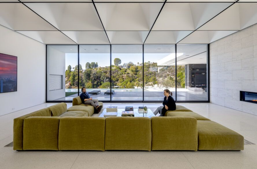 Couches arranged in a horseshoe under a grid of skylights with a view to the hills.