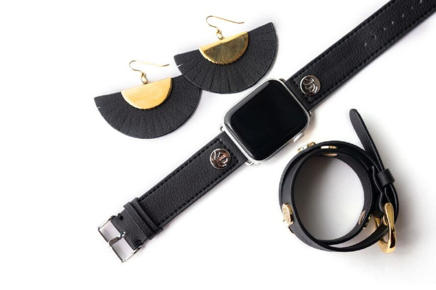 A pair of black semi-circle earrings, a black watch and a black bracelet against a white background.