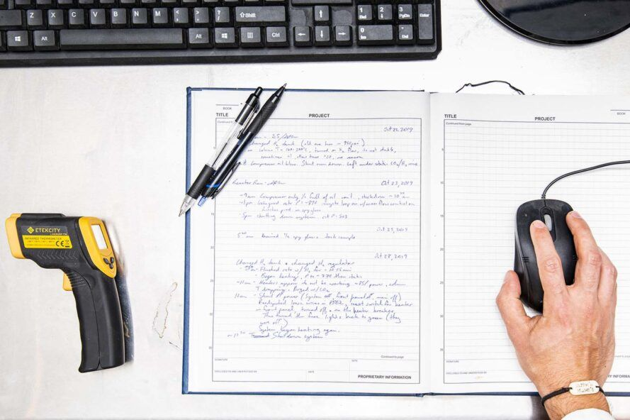A work desk with a yellow and black tool, a notebook and a hand holding a computer mouse.