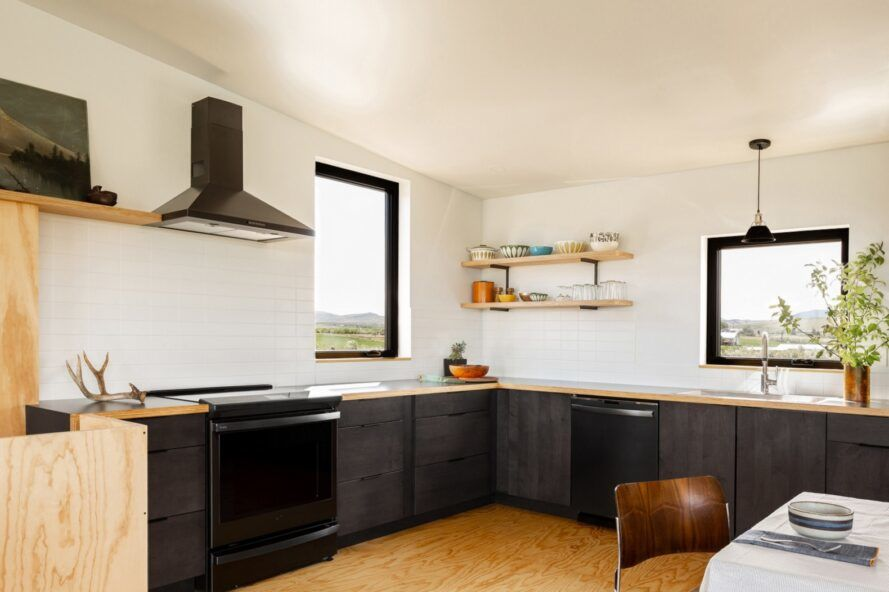 A kitchen with black counters and appliances and white walls.