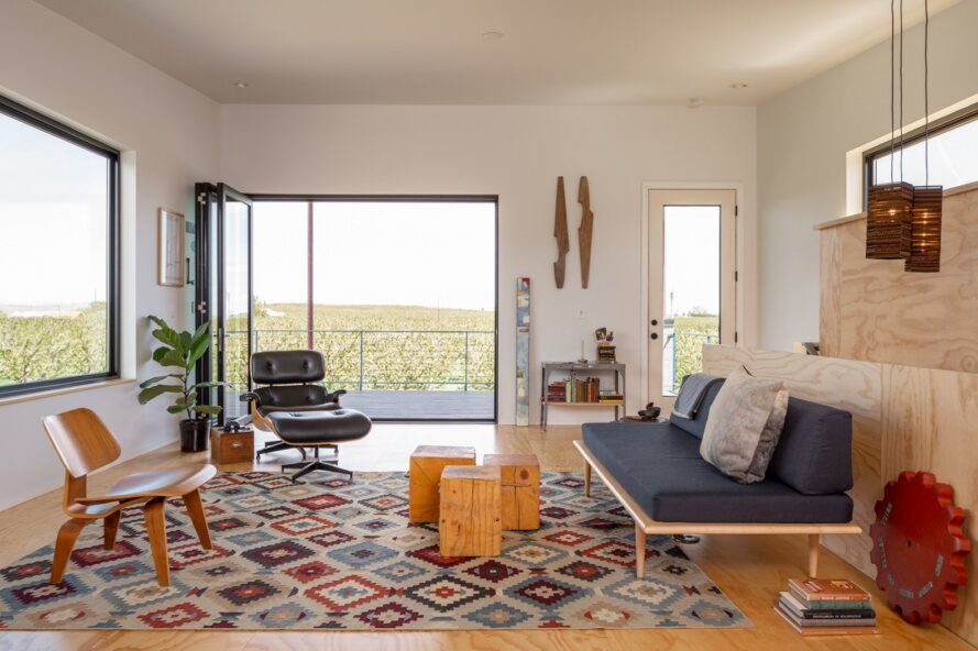 A living room with blue sofa and patterned rug.