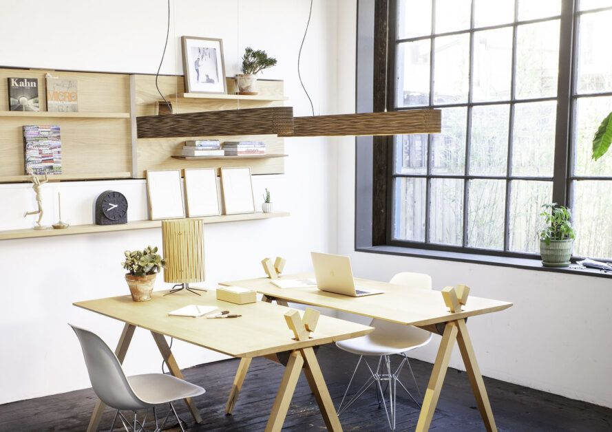 Lighting fixtures above two wood desks in an office space.