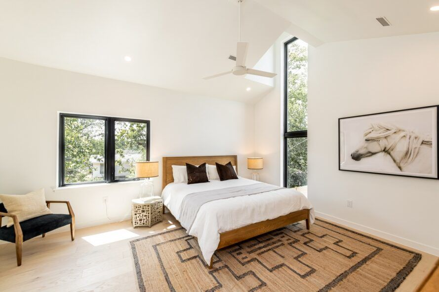 A neutral bedroom with white walls, ceiling and floors.  A woven rug sits under a white bed, and two large windows show some greenery outside.