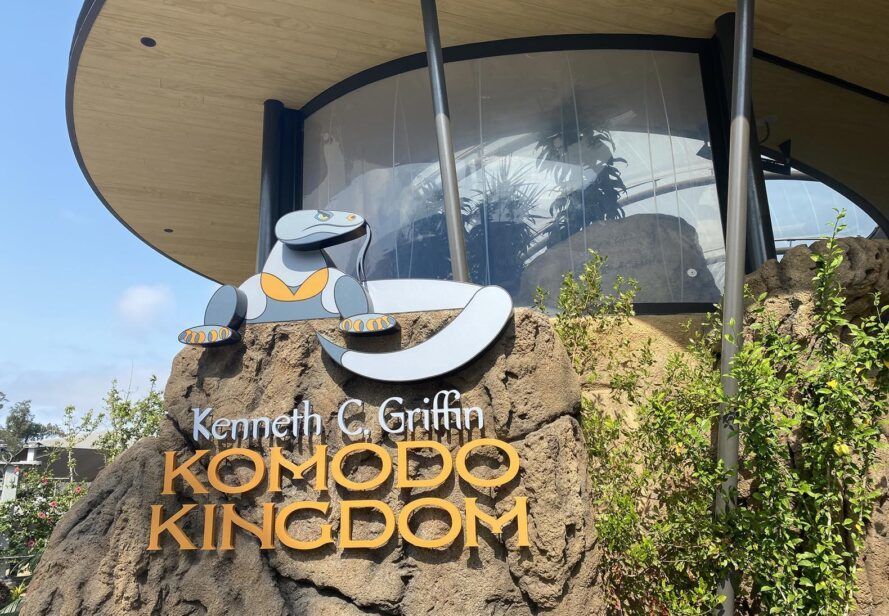 """The exterior of a zoo building with a sign reading """"Kenneth C. Griffin Komodo Kingdom."""""""