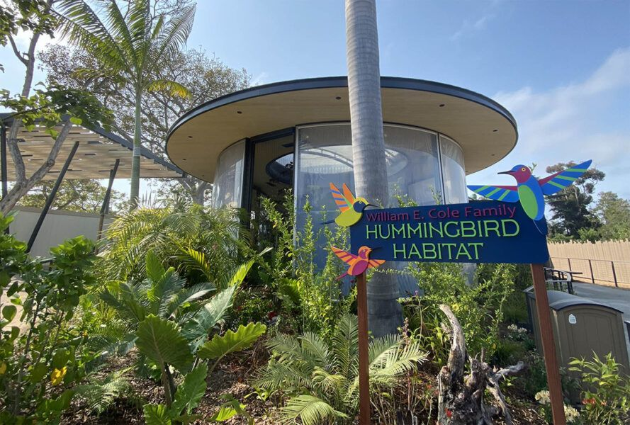 """The exterior of a zoo building with a blue sign reading """"Hummingbird Habitat."""""""