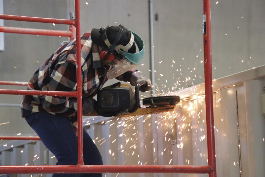Sparks flying as a person with a saw works on a shipping container.
