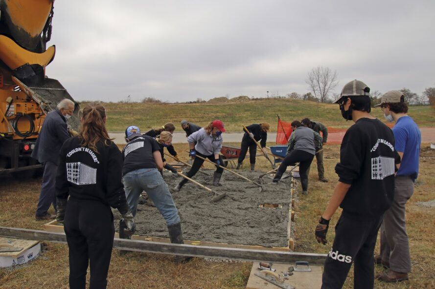 A team laying the foundation for a tiny home.