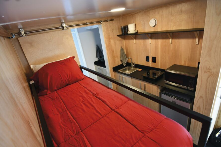 A red bed next to a kitchenette inside a tiny home.