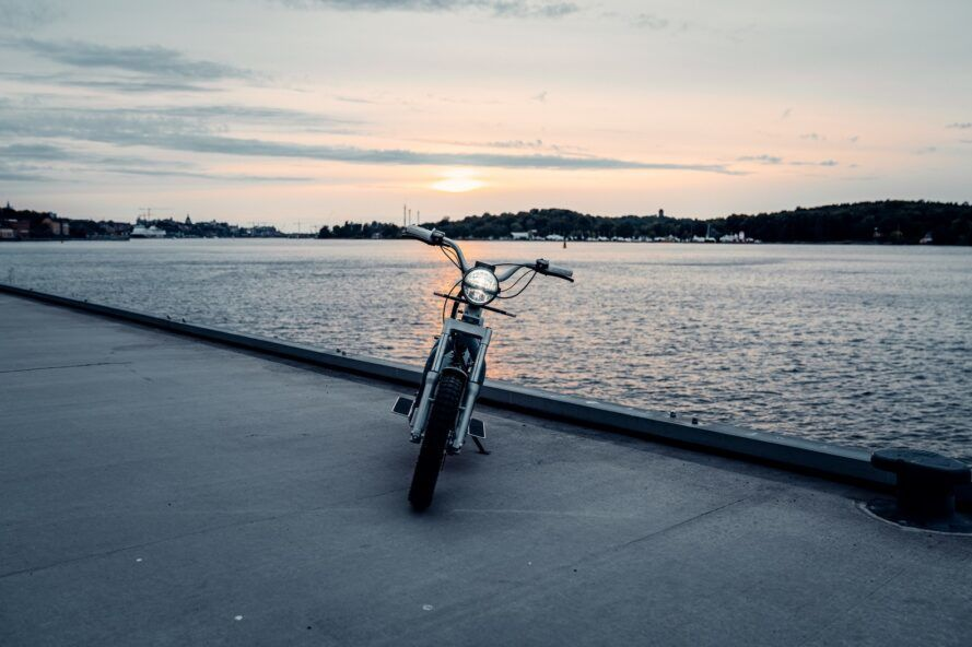 The front of an electric moped parked on a dock by the water.