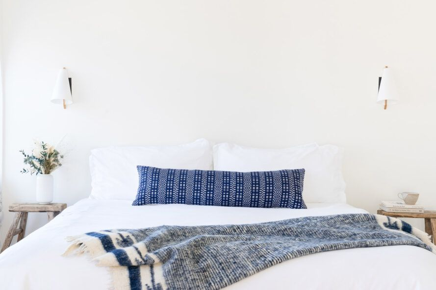 A white bed with a long blue pillow and blue blanket.