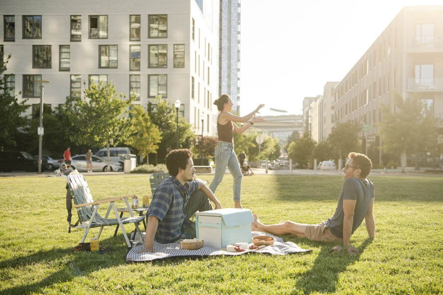 A group of people picnicking on the grass with the cooler between them.