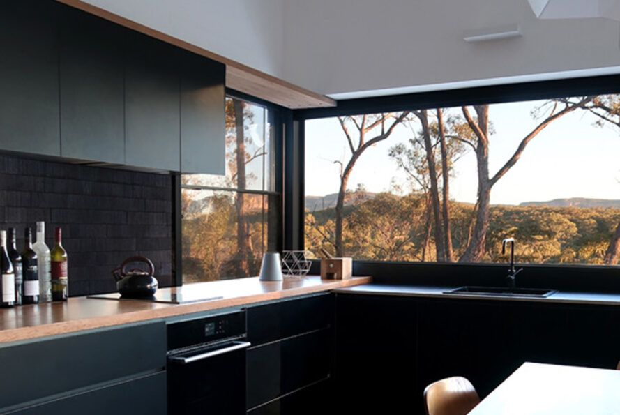 A kitchen with black cabinets with wood countertops. A large window above the sink overlooks a forest.