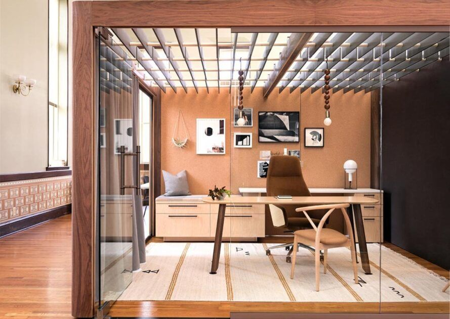 An office space with a wood frame and glass walls that look into a room with a desk and chair.