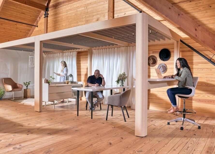 Three people working in an office space completely made of wood.