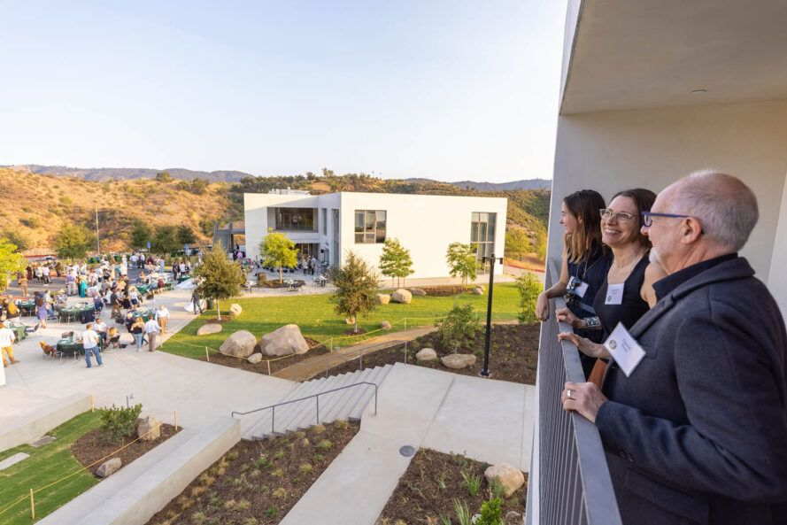 On the right, people looking off a balcony to a green campus courtyard to the left.