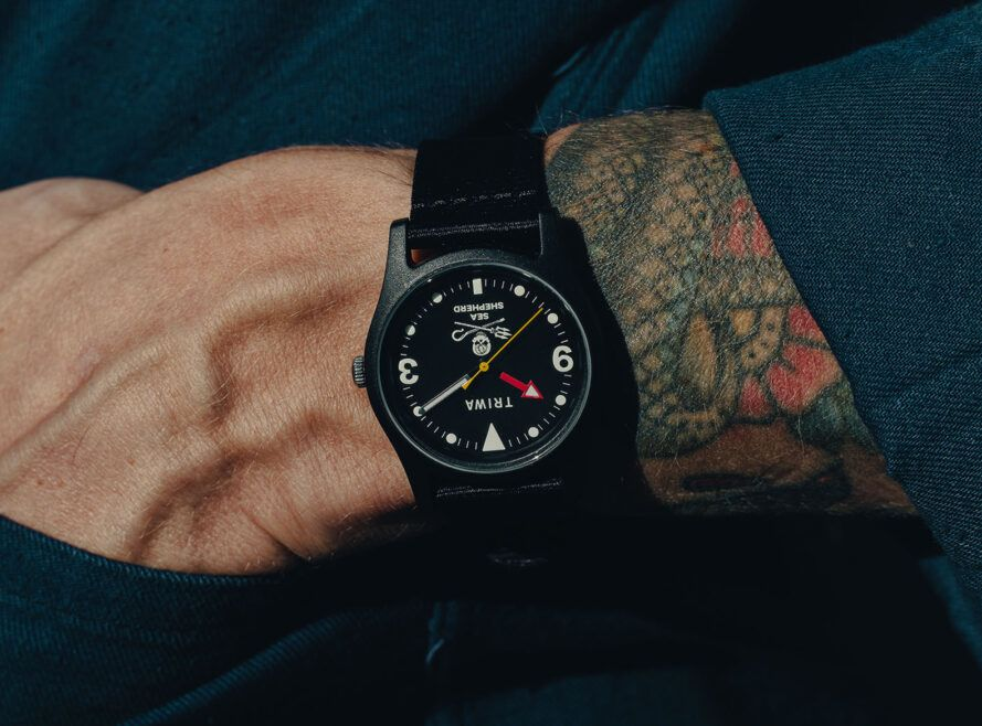 A tattooed arm with a watch on the wrist.