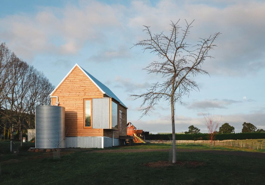 A green yard with a simple wood house with an attached steel water tank.