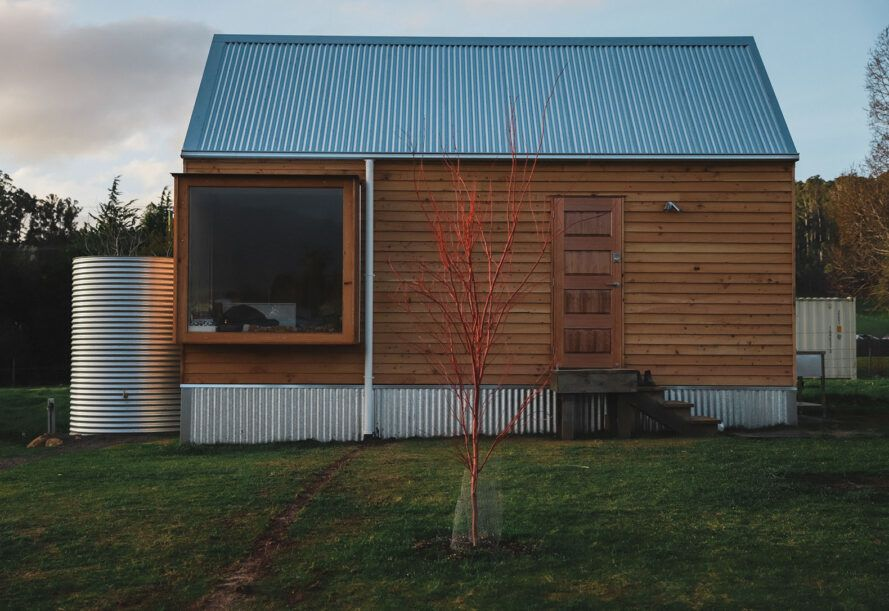 The front of a simple wood house with a steel water tank to the left and a small red tree in front of the house.