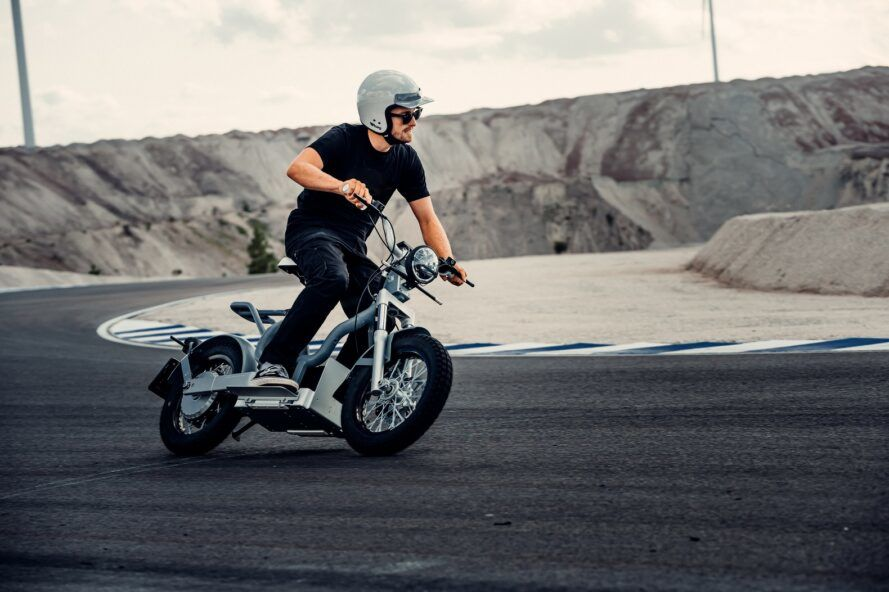 A person wearing a helmet and driving an electric moped.