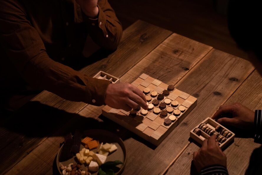 An overhead view of a person playing a wooden board game.