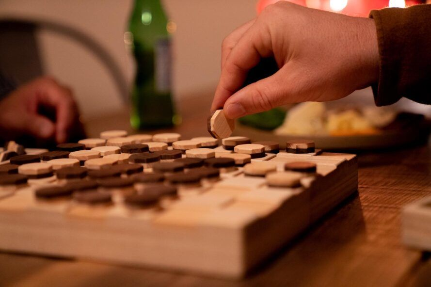 A person playing a wooden board game.