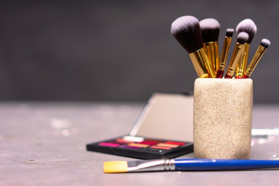 A table with a cup of makeup brushes, a paint brush and a makeup palette on it.