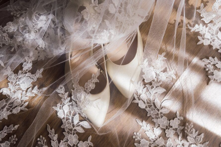white shoes covered by a wedding veil