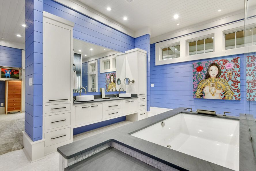 A bathroom with blue walls and white counters.