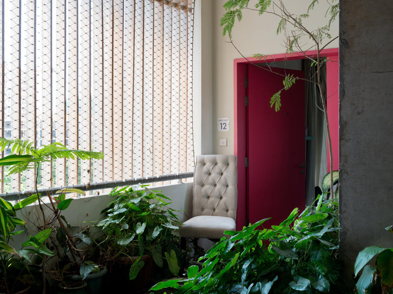 Red apartment entry door surrounded by plants