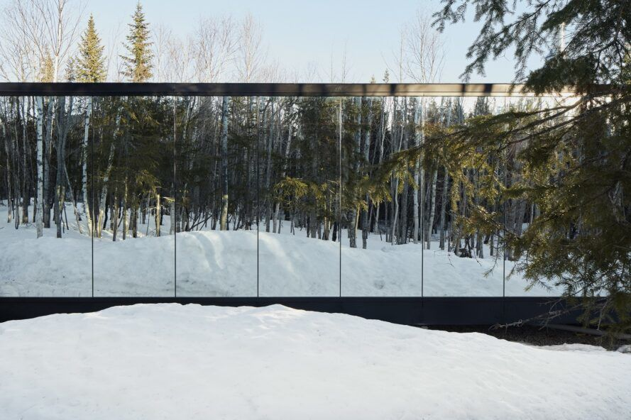 Building with a mirror-like glass that reflects the snow it sits on