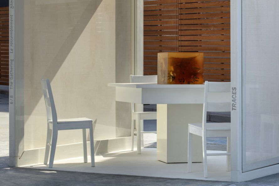 Four chairs and a table with a cube on the table