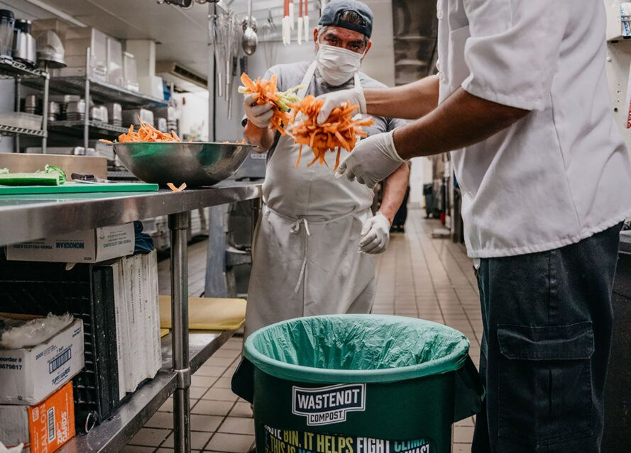 Two people in a kitchen putting items into a composting bin.