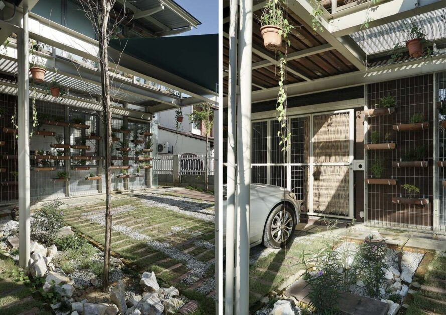 To the left, a green courtyard. To the right, a parking area next to a home.
