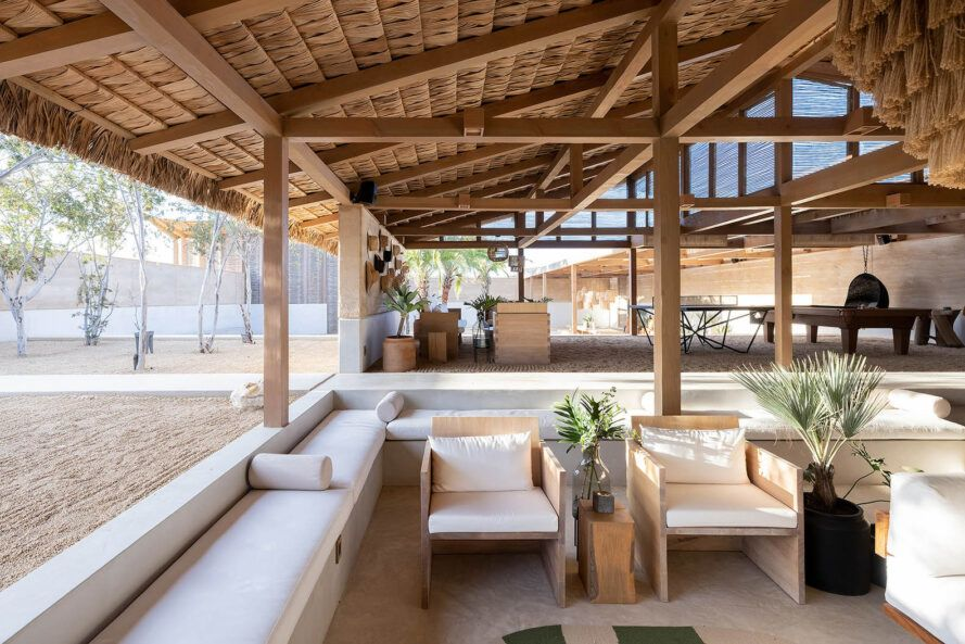 A bright indoor/outdoor area with white couches and chairs.