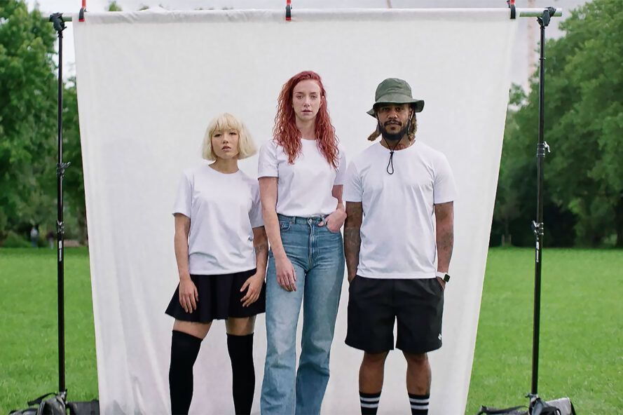 Three people against a white backdrop wearing white t-shirts.