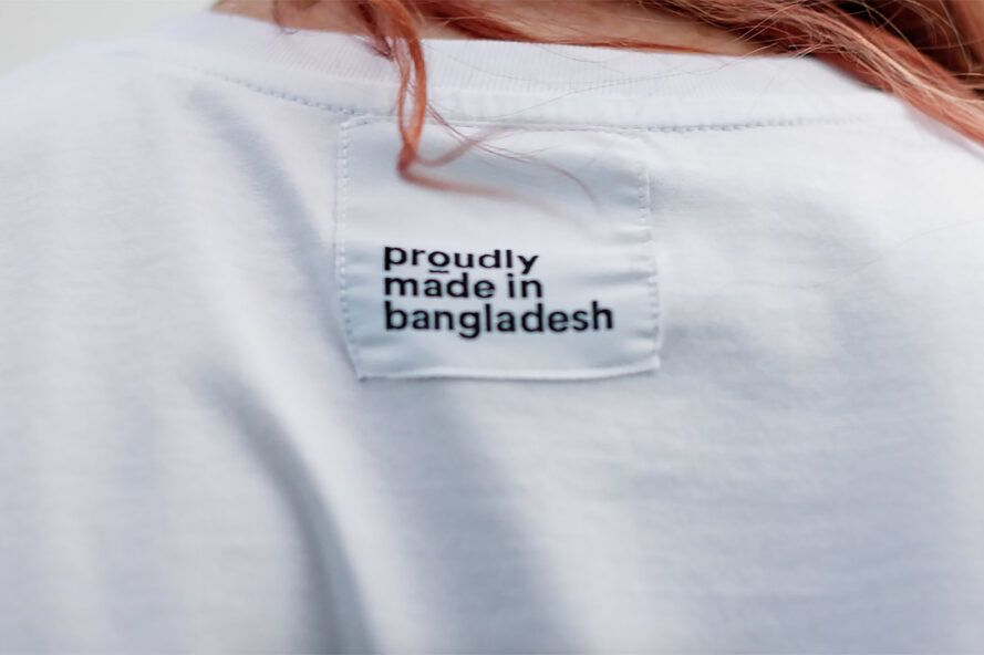 """A person wearing a white t-shirt with a label reading """"proudly made in bangladesh."""""""